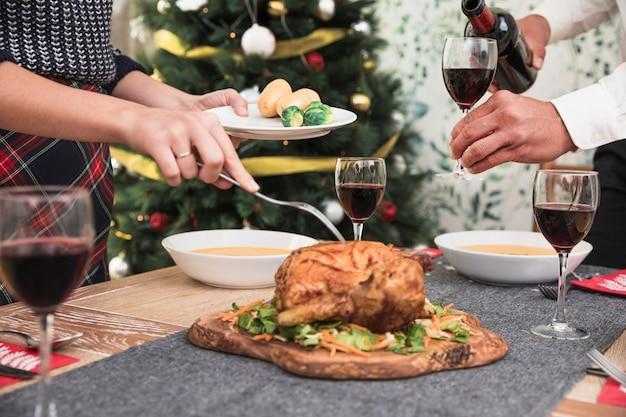 Femme prenant un poulet cuit au four de la table de fête Photo gratuit