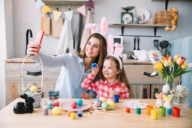 Femme prenant selfie avec sa fille près d'oeufs de pâques Photo gratuit