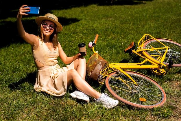 Femme prenant un selfie avec son vélo Photo gratuit
