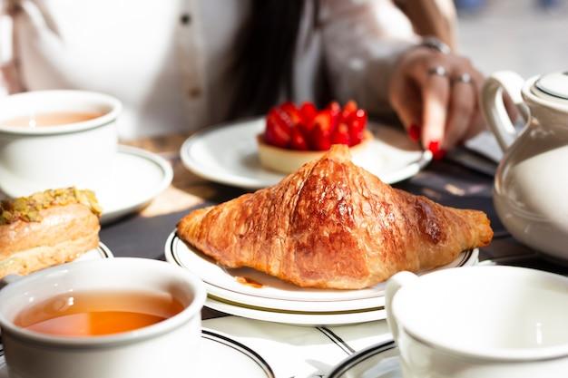Femme prenant son petit déjeuner avec assortiment de pâtisseries Photo gratuit