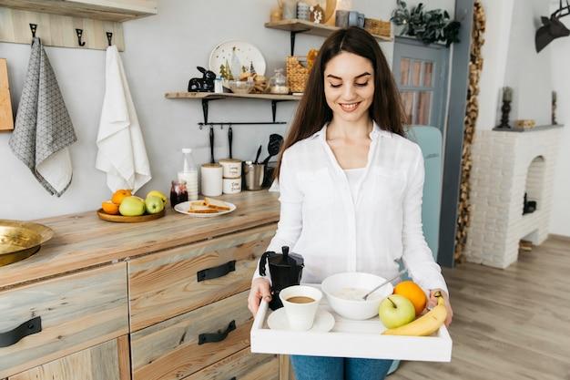 Femme prenant son petit déjeuner à la cuisine Photo gratuit