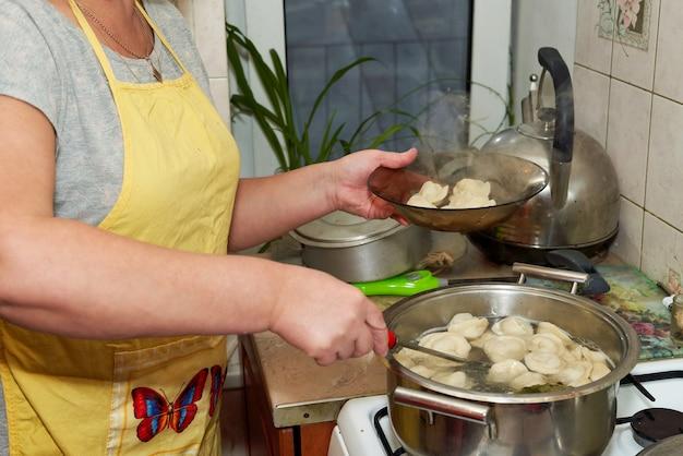 La Femme Prend Des Boulettes Chaudes Cuites De La Casserole Dans Une Assiette Transparente. Cuisine à La Maison Photo Premium