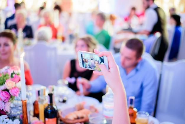 Femme Prend Selfie Sur Son Iphone Assis à La Table Du Dîner Photo Premium