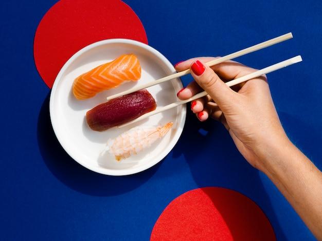 Femme, prendre, à, baguettes, a, sushi thon Photo gratuit
