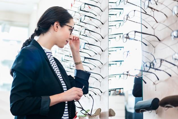 Femme, prendre, lunettes, hors plateau, dans, opticien, magasin Photo Premium