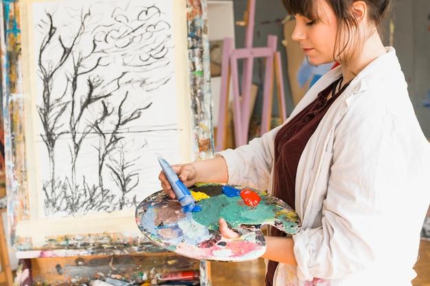 Femme préparant une palette de couleurs pour peindre à l'atelier Photo gratuit