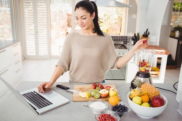 Femme, préparer, jus fruits, pendant, travailler, sur, ordinateur portable Photo Premium
