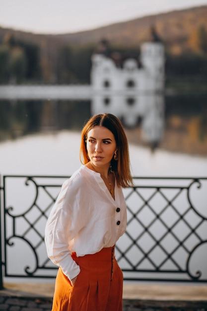 Femme près du château et du lac posant Photo gratuit
