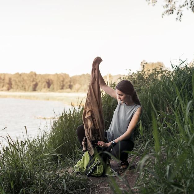 Femme près du lac enlever le sweat-shirt du sac Photo gratuit