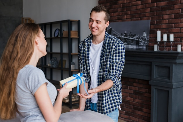 Femme présentant un cadeau à l'homme à la maison Photo gratuit