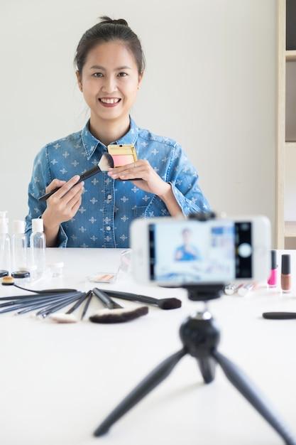 Femme Présente Produit De Beauté Et Diffusion De Vidéos En Direct Sur Le Réseau Social Par Internet à La Maison, Concept De Blogueur De Beauté. Photo Premium