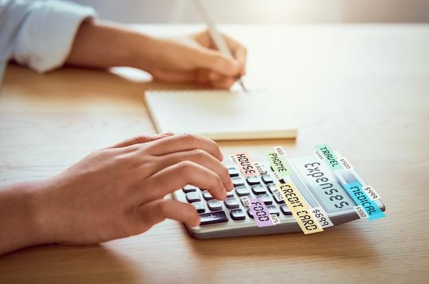 Femme presse calculatrice pour calculer les dépenses de revenu et les plans pour dépenser de l'argent sur le bureau à domicile. Photo Premium