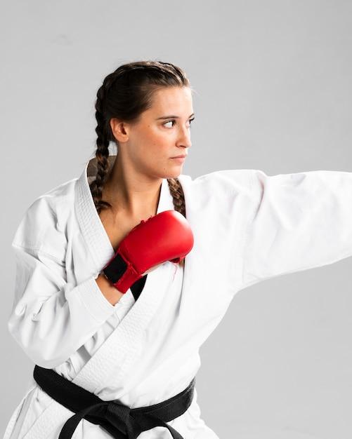 Femme prête à se battre avec des gants de boxe sur fond blanc Photo gratuit