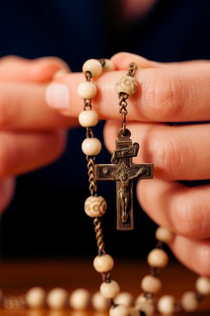 Femme priant avec chapelet à dieu Photo Premium