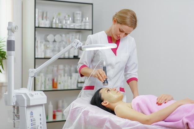 Femme professionnelle d'appliquer la crème verte avec une brosse Photo gratuit