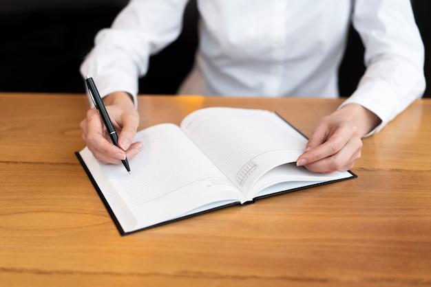 Femme professionnelle écrit dans l'ordre du jour Photo gratuit