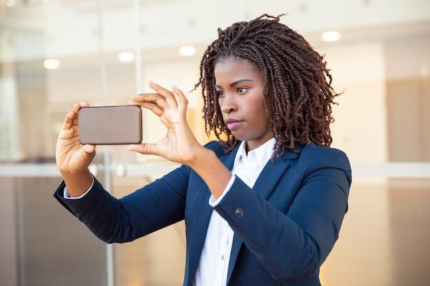 Femme professionnelle prenant photo sur téléphone portable Photo gratuit
