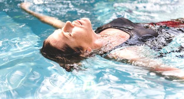 Femme profitant de l'eau dans une piscine Photo gratuit