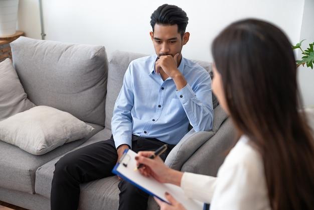 Femme psychiatre écrivant des informations sur un patient jeune asiatique tout en parlant de sa maladie. Photo Premium