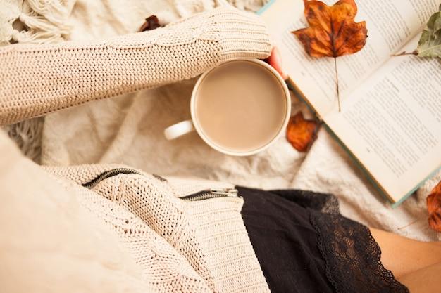 Femme en pull chaud et plaid à carreaux avec une tasse de café au lait dans les mains, assis avec livre Photo Premium