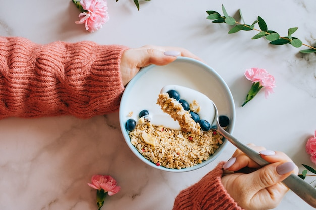 Femme en pull de laine corail mangeant un bol de petit-déjeuner avec muesli et yaourt, baies et noisettes Photo Premium