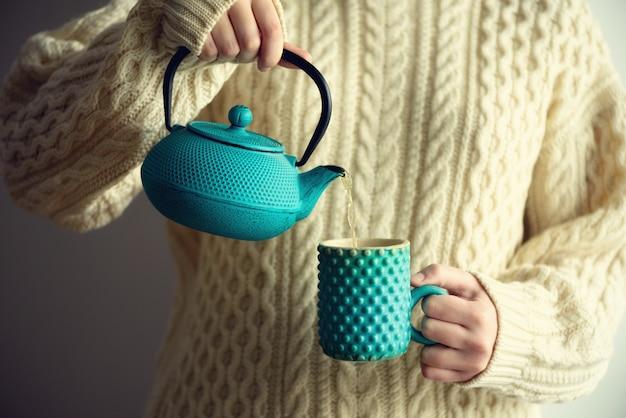 Femme en pull de laine tricoté avec une théière turquoise et des tisanes dans une tasse à la main. espace de copie. concept de vacances d'hiver et de noël Photo Premium