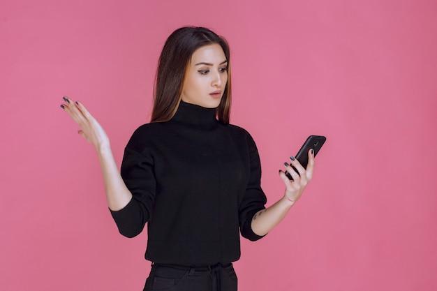 Femme En Pull Noir Tenant Un Smartphone Et Envoyer Des Sms Ou Vérifier Les Médias Sociaux. Photo gratuit