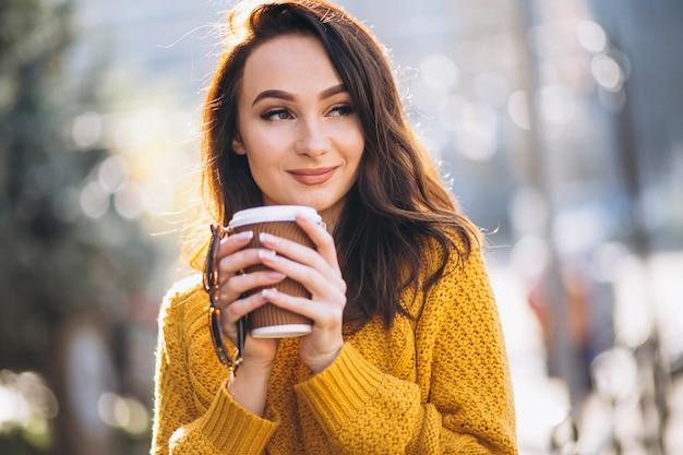 Femme, pull orange, boire café Photo gratuit