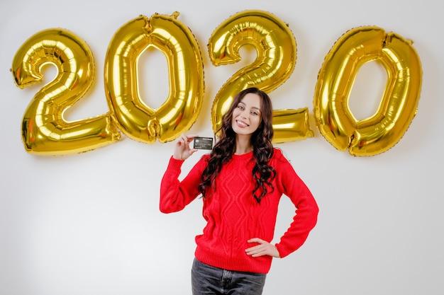Femme en pull rouge détenant une carte de crédit type devant des ballons de nouvel an 2020 Photo Premium