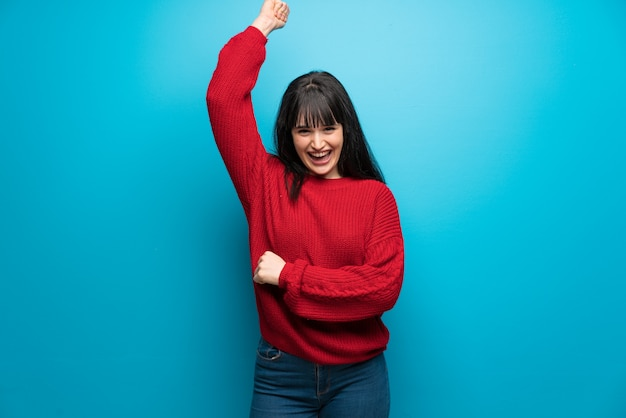 Femme, pull rouge, mur bleu, célébrer, victoire Photo Premium