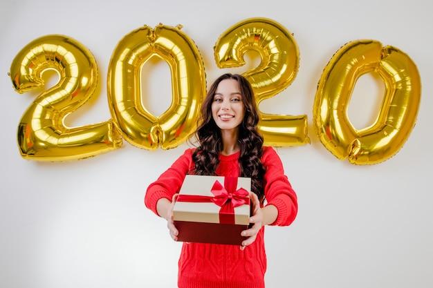 Femme En Pull Rouge Ouvrant Le Cadeau De Noël Devant Les Ballons Du Nouvel An 2020 Photo Premium