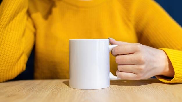 Femme En Pull Tenant Une Tasse Sur Une Table En Bois Photo gratuit