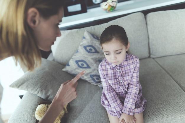Une femme punit une fille et grimace son doigt. Photo Premium