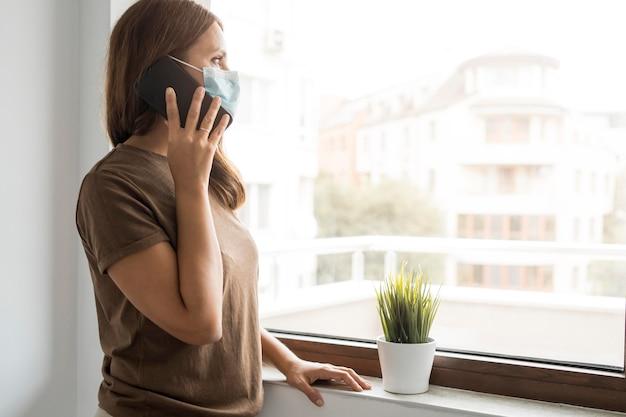 Femme En Quarantaine à La Maison Parler Au Téléphone Tout En Regardant Par La Fenêtre Photo gratuit