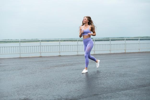 Femme qui court le long du lac long shot Photo gratuit