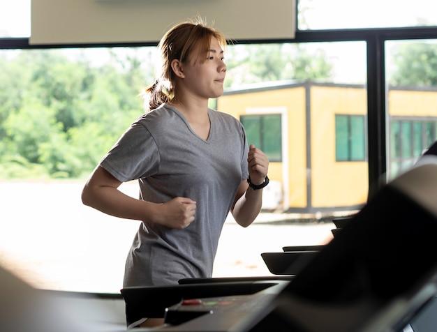 Femme qui court sur un tapis roulant électrique à la salle de fitness Photo Premium