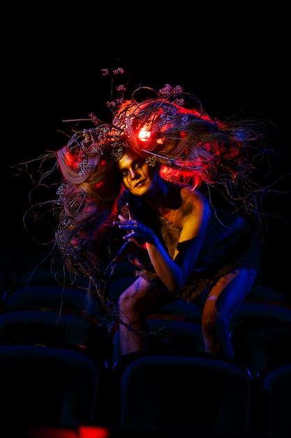 La Femme Qui Joue Le Rôle D'un Fantôme Ou D'un Esprit Dans Le Théâtre Est Assise Entre Les Rangées De Chaises Photo Premium
