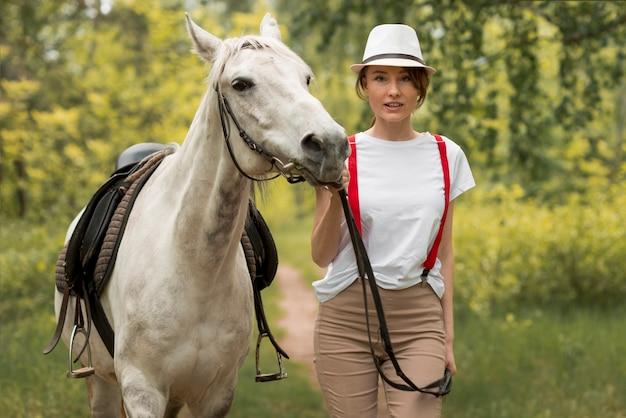 Femme qui marche avec un cheval à la campagne Photo gratuit