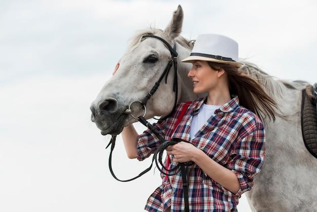 Femme qui marche avec un cheval sur la plage Photo gratuit