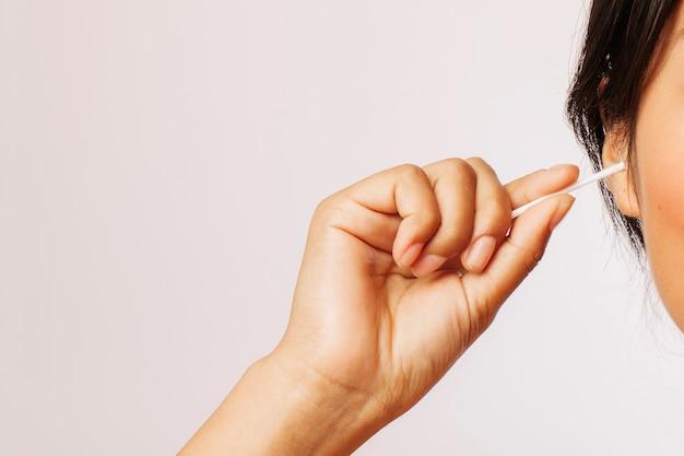 Femme qui nettoie ses oreilles avec des écouvillons en coton Photo gratuit