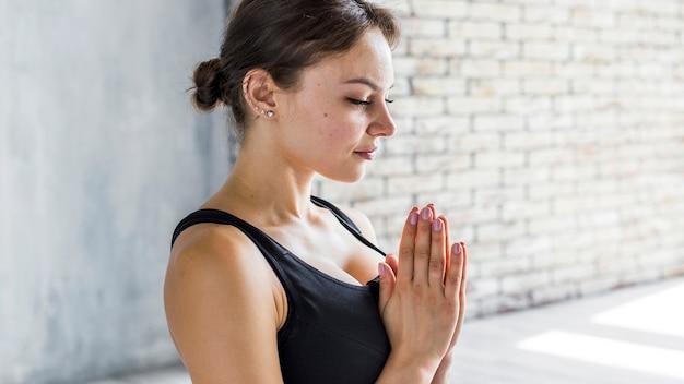 Femme Qui Respire Lors D'une Pose De Yoga Namaste Photo gratuit