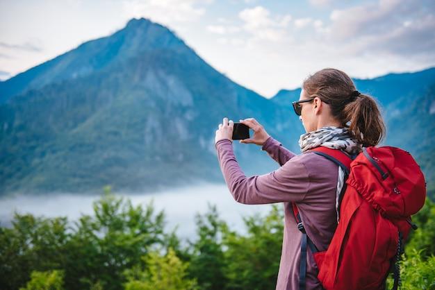 Femme de randonnée sur la montagne et de prendre des photos avec le téléphone intelligent Photo Premium