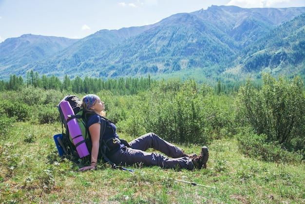 Femme randonneur avec sac à dos assis sur l'herbe verte et se détendre avec les yeux fermés Photo Premium