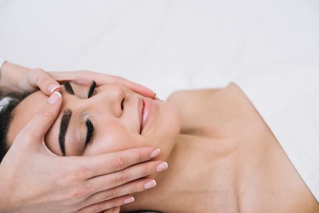 Femme recevant un massage relaxant du visage Photo gratuit