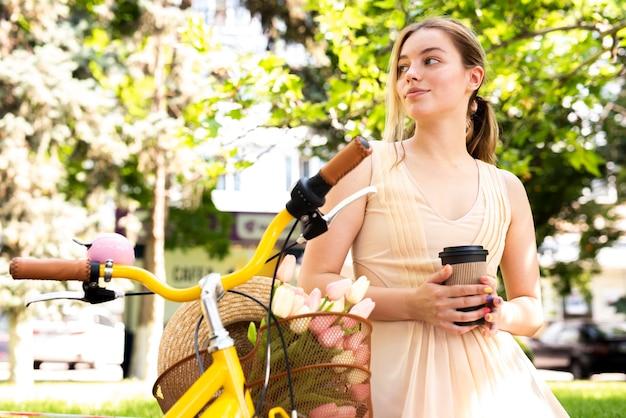 Femme à la recherche de suite et s'appuyant sur un vélo Photo gratuit