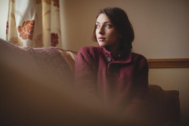 Femme Réfléchie Assise Sur Un Canapé Dans Le Salon Photo gratuit