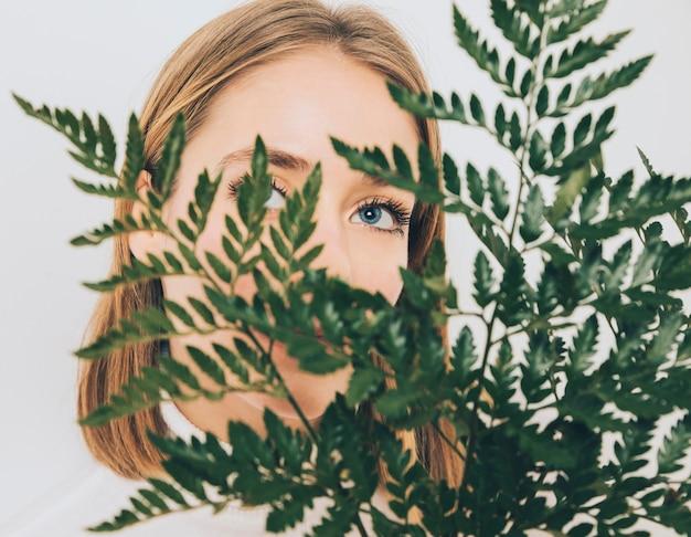 Femme réfléchie couvrant le visage avec des feuilles de fougère Photo gratuit