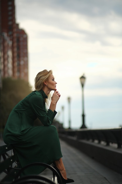 Femme réfléchie en robe verte est assis sur le banc Photo gratuit