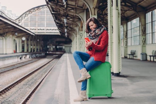 La femme a un regard positif, est assis jambes croisées au sac, tient le téléphone Photo Premium