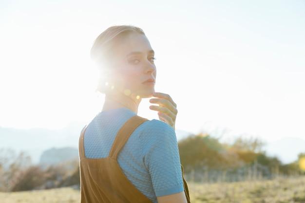 Femme regardant au-dessus de l'épaule avec la lumière du soleil Photo gratuit